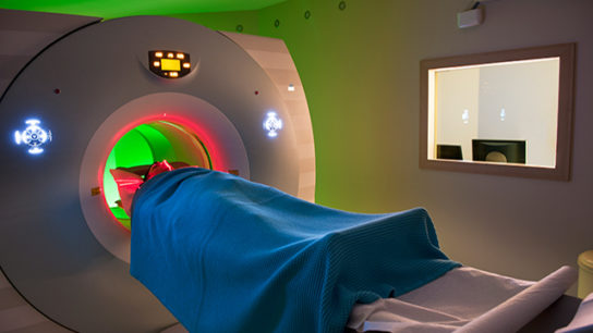 A patient undergoes a tunnel PET/CT scan.