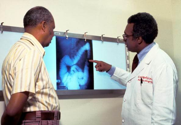 Doctor examining x-ray of colon with patient.