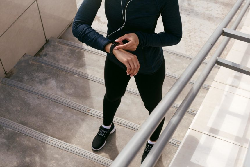 A woman stands on a staircase and checks a fitness tracker on her wrist.