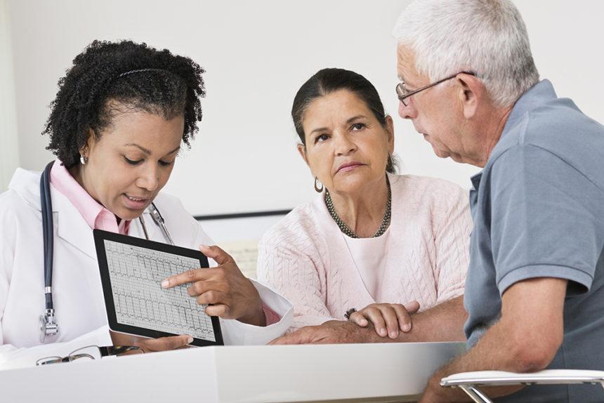 Doctor explaining heart rate to elderly patient EKG