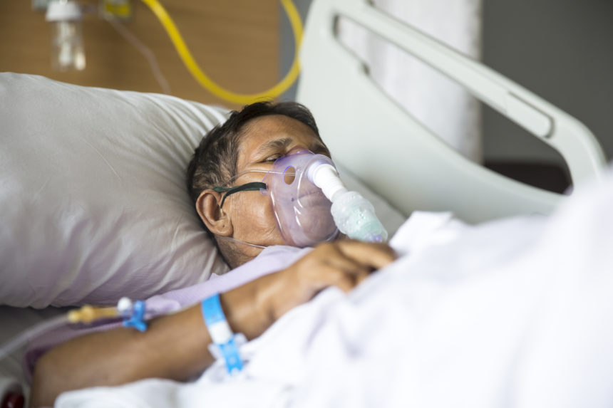 Patient lying on Hospital bed with ventilator mask on her nose.
