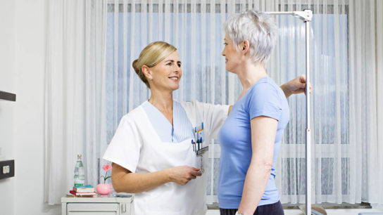 Measuring an adult patient's height.