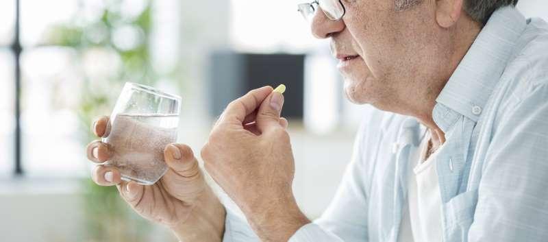 elderly man taking pill