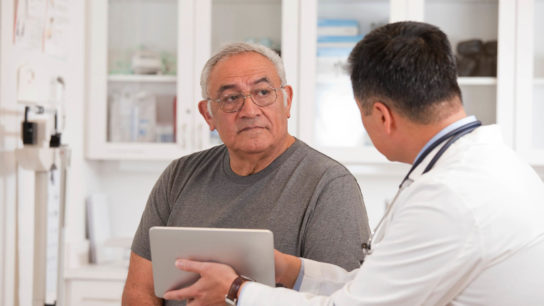 Man listening to doctor holding a tablet