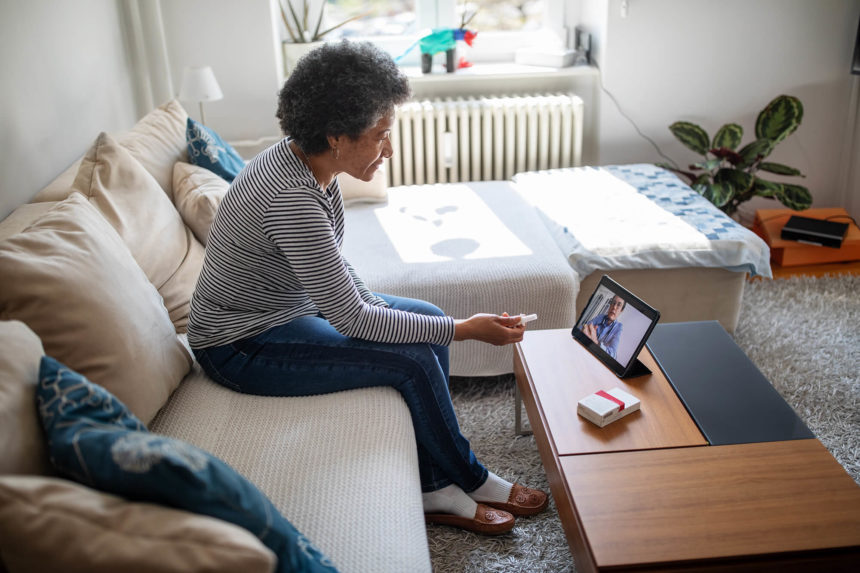 A cancer survivor is contacted by a clincian remotely.