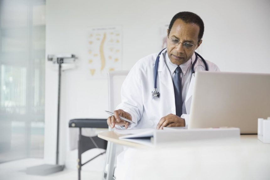 A doctor sits at his desk, working hard.