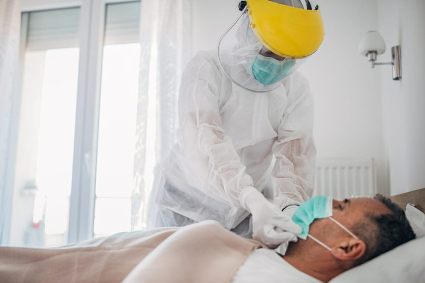 Doctor putting face mask on hospitalized patient