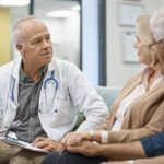 Doctor talking to couple in waiting room