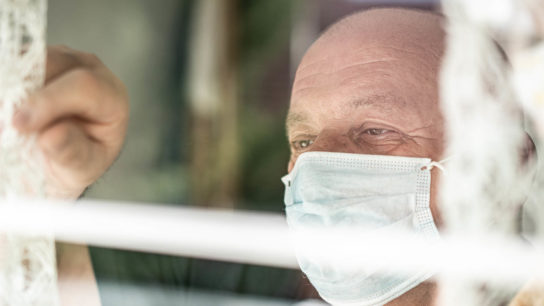Masked male patient looking out of window.