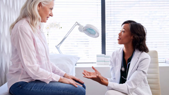 Female patient talking to doctor.