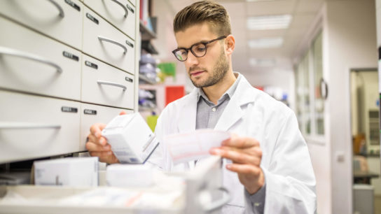 Pharmacist looking at boxed drugs.